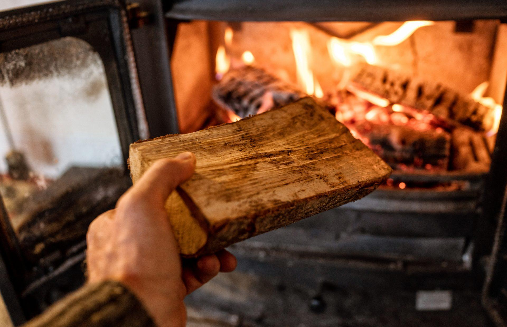 Close-up of a log being put into a hot wood-burning stove.